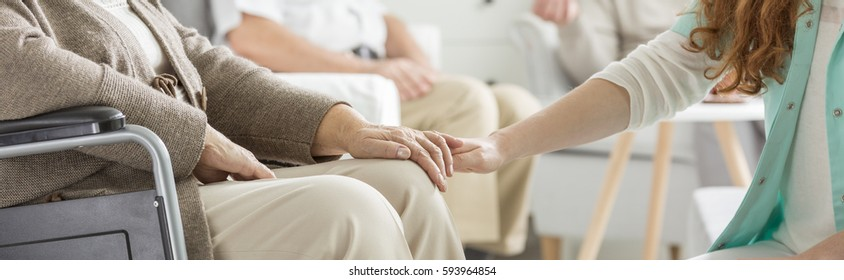 Close-up of young nurse holding her older patient's hand