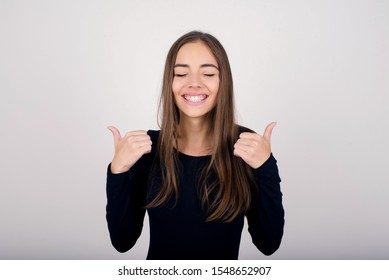 Closeup of young optimistic female isolated on grey background showing thumbs up with positive emotions of content and happiness. Copyspace, concept of satisfaction with quality and recommendation.