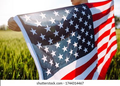 Closeup of a young patriotic farmer stands among new harvest. Boy walking with the american flag on the green wheat field celebrating national independence day. 4th of July concept.