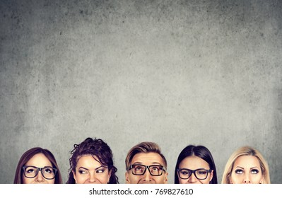 Closeup of young people heads standing near a gray concrete wall. A diverse business team and brainstorming concept