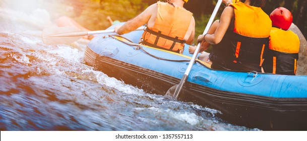 Close-up of young people rafting on the river turbulent flow with sunbeam. Extreme and enjoyment sport.