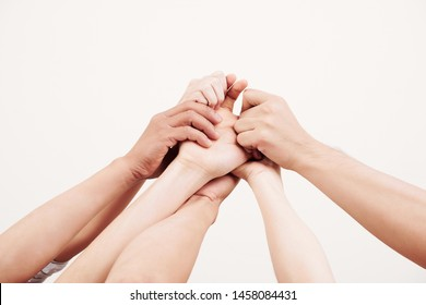 Close-up of young people raising their arms up and holding hands with each other they are friendly team