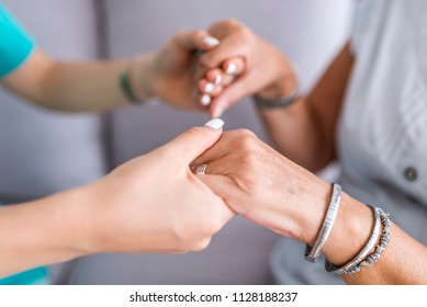 Close-up of young person's hand holding elderly person's hand as sign of caring for seniors. Helping hands, care for the elderly concept. Senior person thanks the nurse