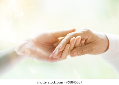 Close-up of young person's hand holding elderly person's hand as sign of caring for seniors