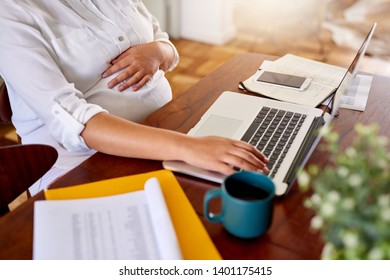 Closeup of a young pregnant woman sitting at her dining room table working from home with a laptop while on maternity leave