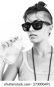 Close-up of young pretty cute brunette girl in sunglasses  Beautiful woman drinking water in spring day. Outdoor summer black white portrait