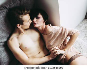 Close-up of young romantic couple is kissing and enjoying the company of each other at home.