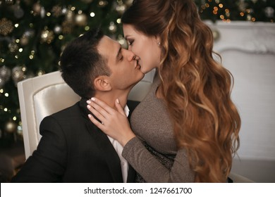 Close-up of young romantic couple is kissing at home. Happy smiling woman emrace her handsome man.