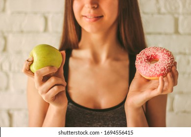 Closeup young sexy fitness girl holding apple and donut in hands. Beautiful slim sports woman choosing between healthy fruit or sweet donut temptation. Healthy lifestyle, fitness dieting, weightloss
