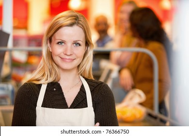 Closeup of a young shop assistant with customer in the background