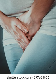 Closeup young sick woman with hands holding pressing her crotch lower abdomen. Medical or gynecological problems, healthcare concept