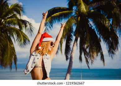 closeup of a young slim sexy redhead girl in sunglasses and a red hat of Santa Claus on Christmas in the New Year on background of blue sky in the summer sea palm in the garden on holiday lifestyle