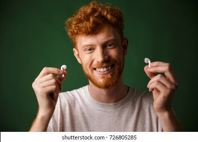 Close-up of young smiling curly redhead bearded young man in white tshirt, showing  wireless headphones, over green background