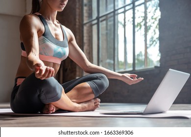 Closeup young sporty fit slim woman coach do practice video online training hatha yoga instructor modern laptop meditate Sukhasana posture relax breathe easy seat pose gym healthy lifestyle concept.