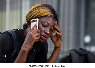 close-up of young student sad and having problem speaking on the phone head down in the city in daylight