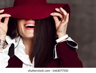 Closeup of young stylish woman brunette in black jacket and white shirt pulls down hat brim hiding her eyes and laughs on grey background