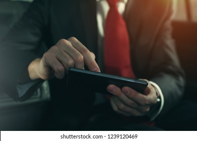 Close-up - young successful businessman sitting in the car. Handsome man manager working using his smartphone.
