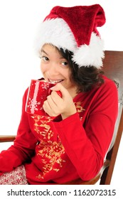 Close-up of a young teen girl looking up as she happily sips hot chocolate with marshmallows.  She's wearing a Santa hat and her pajamas.  On a white backgroundl