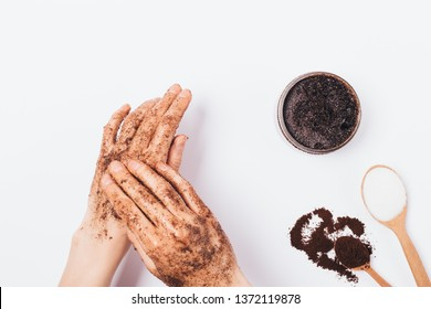 Close-up young woman apply cosmetic scrub of fresh ground coffee, sugar and coconut oil on her hands, top view on white table.