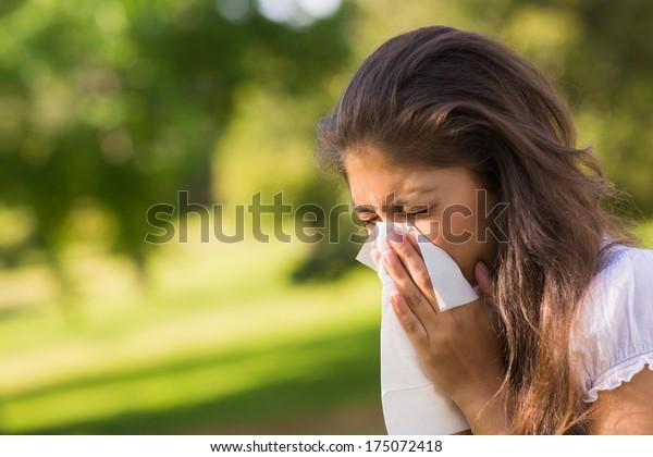 特寫的一個年輕女子吹鼻子用紙巾在公園