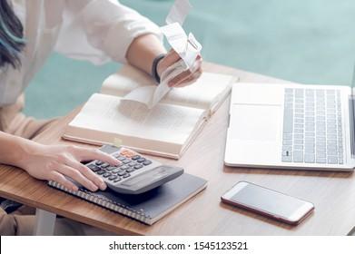 Nahaufnahme einer jungen Frau, die das Rechnungsbudget berechnet, eine Quittung mit Taschenrechner besitzt und auf dem Sofa im Wohnzimmer sitzt.