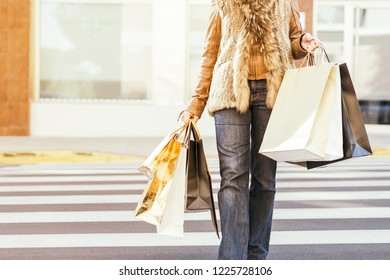 Close-up of young woman carrying shopping bags while walking along the street. Happy Life Style Concept.