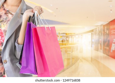 Close-up of young woman carrying shopping bags in shopping mall. Happy Life Style Concept.