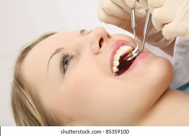 Close-up of young woman checking her teeth at dentis's isolated
