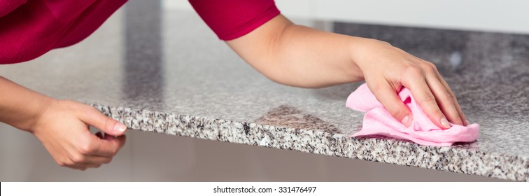 Closeup of young woman cleaning granite countertop
