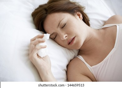 Closeup of young woman with cold sleeping in bed
