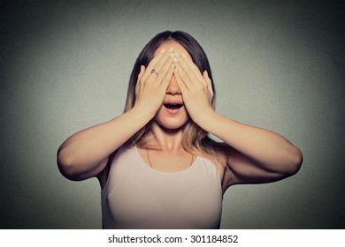 Closeup young woman covering her eyes with hands doesn't see
