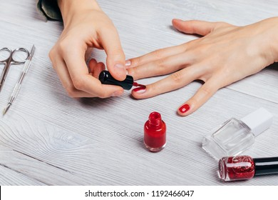 Close-up young woman does manicure to herself. Female's hands apply red polish on nails next to scissors, bottles of lacquer and top cover on white table.