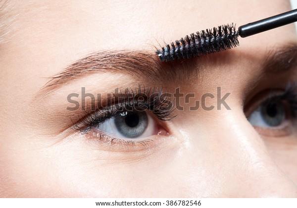 化粧ブラシをする若い女性の接写