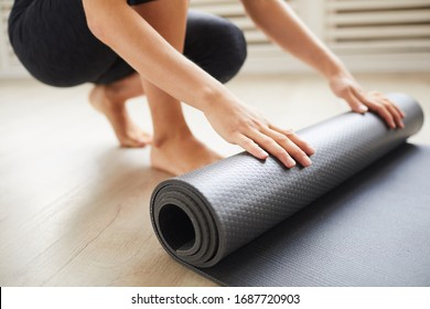 Close-up of young woman with exercise mat preparing for sports training