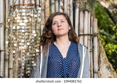 Closeup of young woman face looking up happy smiling in zen bamboo garden with shiny decorations wind chimes