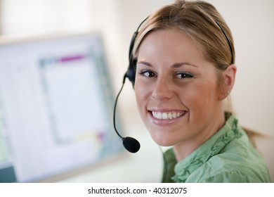 Close-up of a young woman in front of a computer, wearing a headset and smiling at the camera. Horizontal format.
