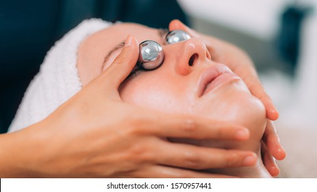 Close-up of a young woman getting lymphatic drainage treatment with Chinese meditation balls.
