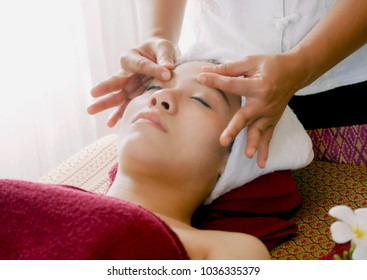 Closeup of young woman getting spa face massage at beauty salon.