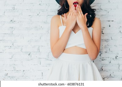 Closeup of Young woman giving surprise look with fashionable summer hat over white wall background