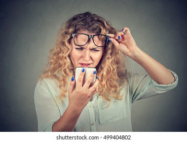 Closeup young woman with glasses having trouble seeing cell phone has vision problems. Bad text message. Negative human emotion facial expression perception. Confusing technology