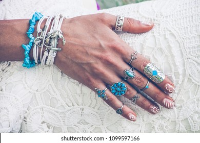 closeup of young woman hand with lot of boho style jewrly, rings and bracelets outdoor summer day