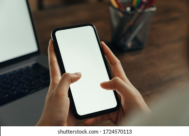 Closeup of young woman hand holding smartphone on the table and the screen is blank, social network concept.