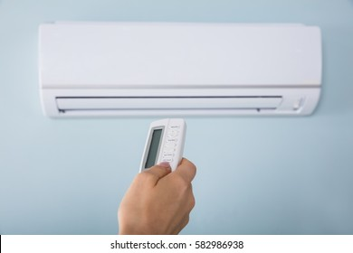 Close-up Of Young Woman Hand Operating Air Conditioner With Remote Control