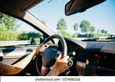 Close-up of a young woman hands driving a car. Selective focus on the driver's hands. The road trip in summer sunny day