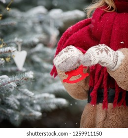 Closeup of a young woman holding in her hands decorations for a Christmas fir in the shape of a horse. Decorated Christmas tree. New Year and Christmas concept
