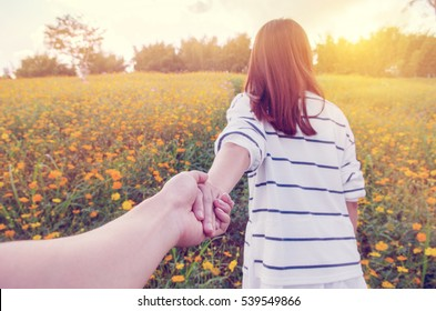 Closeup Young woman holding man hand while leading him on nature outdoor. Couple in love.