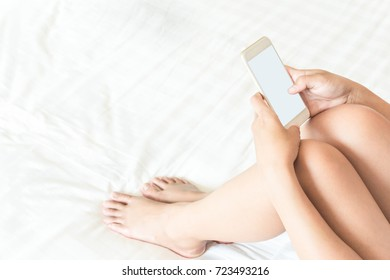 Closeup young woman holding smart phone lying on bed, happy and relax time concept