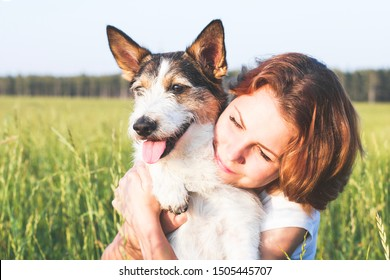 Close-up of a young woman hugs her dog on a meadow. Mixed dog with tongue smiling next to a happy woman outdoors. Evening sunset outside, beloved puppy.