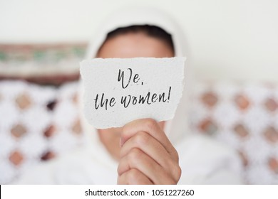 closeup of a young woman indoors wearing a white hijab showing a piece of paper in front of her face with the text we the women written in it