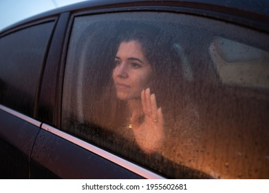 Close-up young woman inside car looking through window place hand on glass with melancholy face.